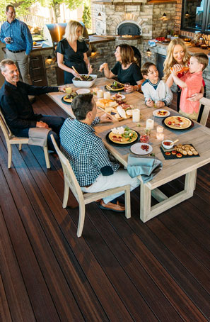Envision Distinction Rustic Walnut family gathering in outdoor kitchen (thumb)